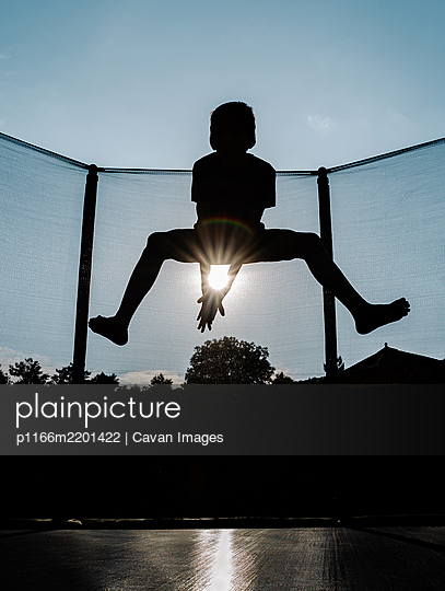 vertical front backlighting photo of a silhouette of a barefoot young boy jumping or flying on a trampoline with net and the sun between arms reflecting sunbeam rays that create a rainbow - p1166m2201422 by Cavan Images