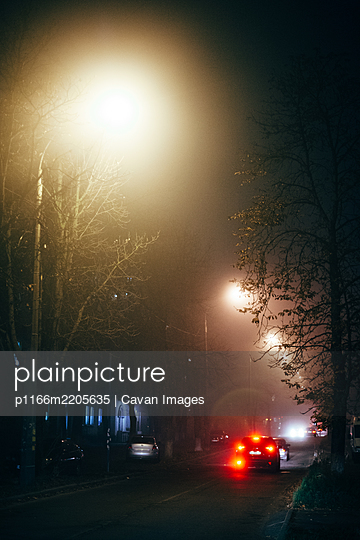 Foggy city street at night during autumn - p1166m2205635 by Cavan Images