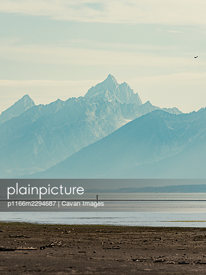 Man on lake with mountains in Grand Teton National Park in Wyoming - p1166m2294687 by Cavan Images