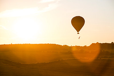 A hot air ballon flies past the setting sun - p1057m931348 by Stephen Shepherd