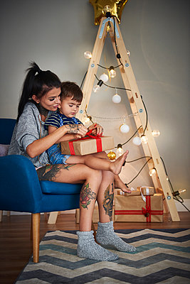 Boy opening Christmas present with his mother at home - p300m2041557 by gpointstudio