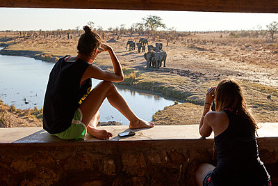 Two women watching a herd of elephants in the river from a viewpoint, Hwange National Park, Zimbabwe - p300m2156817 by Veam