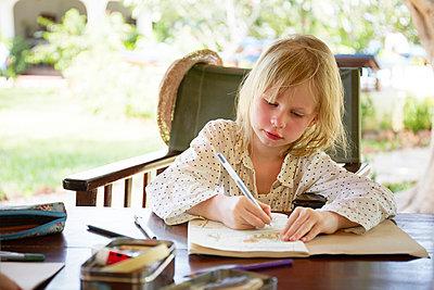 Girl writing in garden - p312m993053f by Anna Kern