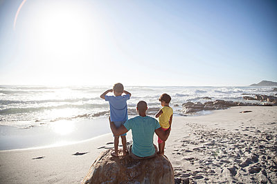 Mixed race father and children sitting on beach - p555m1410111 by Resolution Productions