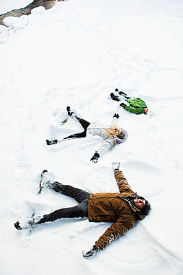 Family making snow angels - p9242954f by Image Source