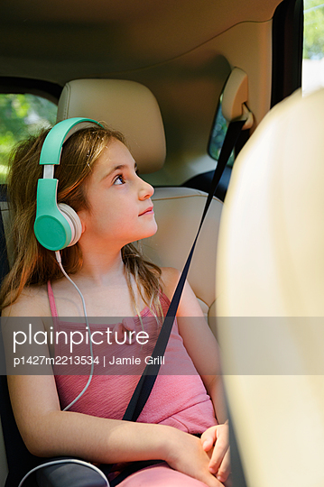 Girl (6-7) listening to music in car - p1427m2213534 by Jamie Grill