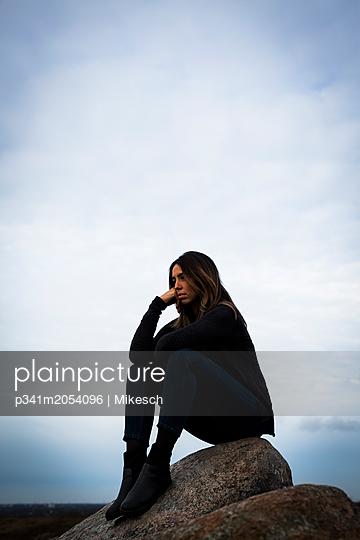 Nachdenkliche Frau sitzt auf einem Findling - p341m2054096 von Mikesch