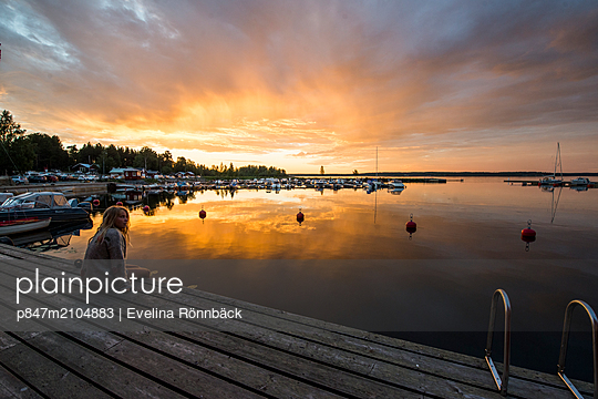 Woman Sitting On Pier Looking Out Over The Sea During Sunset, Norrbotten, Sweden   - p847m2104883 by Evelina Rönnbäck