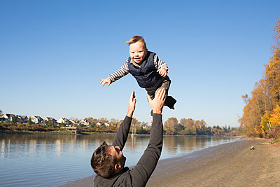 Rear view of happy father throwing daughter while standing at Brae Island Regional Park against clear sky - p1166m1530167 by Cavan Images