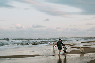 Family with dog enjoying at beach against cloudy sky during sunset - p1166m2034806 by Cavan Images