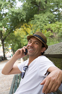 Portrait of smiling Hispanic man talking on cell phone in park - p555m1419104 by REB Images