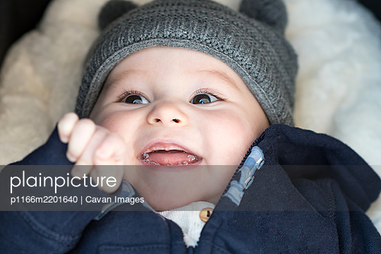A few months old baby in a wool cap looking closely and smiling without teeth - p1166m2201640 by Cavan Images