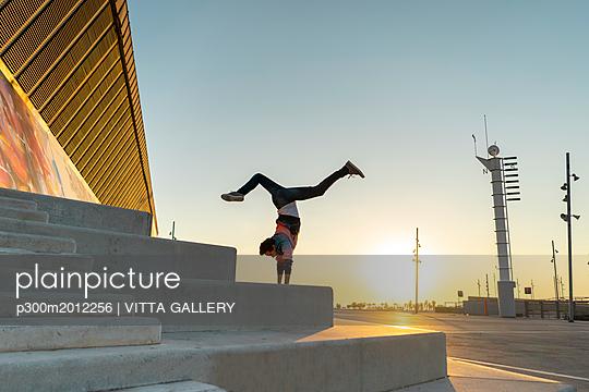 Acrobat doing handstand on stairs at sunrise - p300m2012256 von VITTA GALLERY