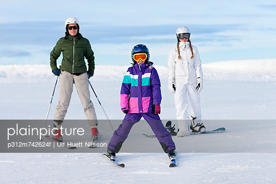 Mother and two daughters skiing