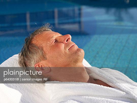 Aelterer Mann in weissem Bademantel am Pool  - p6430318f von senior images RF