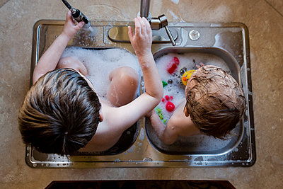 Overhead view of brothers playing with water in sink - p1166m1210625 by Cavan Images