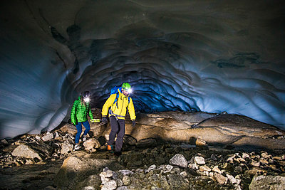 Couple exploring ice cave near Vancouver, Canada. - p1166m2159590 by Cavan Images