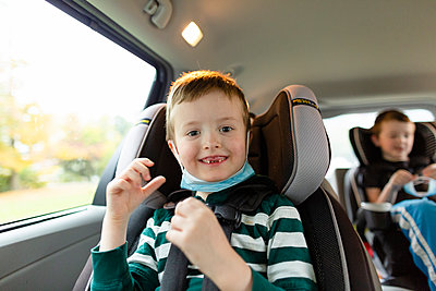 Elementary Age Boy Smiling While Sitting in Car With Face Mask - p1166m2218087 by Cavan Images
