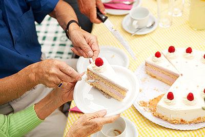 Hands putting cream cake on plates - p300m1205328 by Michelle Fraikin