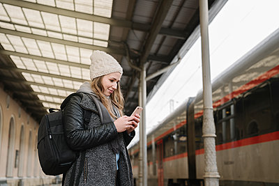 Smiling young woman with backpack standing on platform looking at cell phone, Vilnius, Lithuania - p300m2155213 by Hernandez and Sorokina