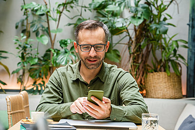 Smiling businessman using mobile phone while sitting at cafe - p300m2227330 by Vasily Pindyurin