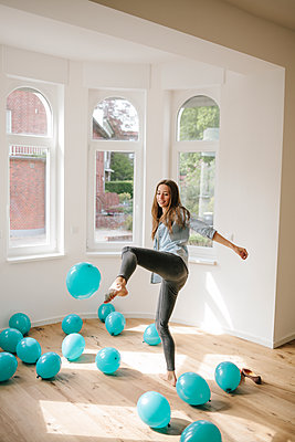 Young woman in new apartment playing with balloons - p586m1064893 by Kniel Synnatzschke