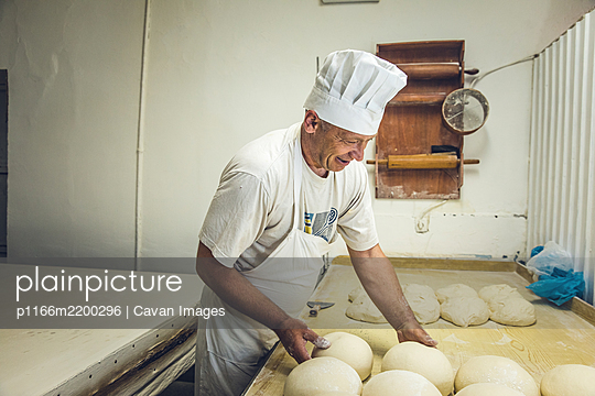 Smiling Man Arranging Dough at a Bakery in Belgrade, Serbia - p1166m2200296 by Cavan Images