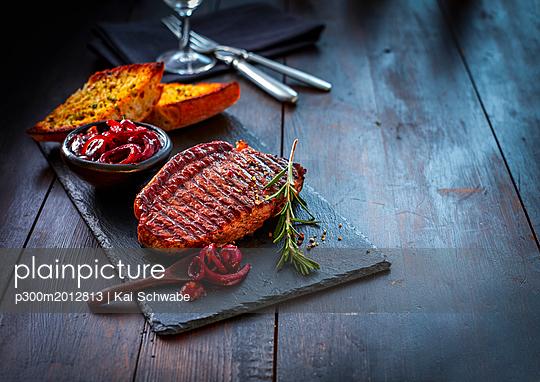 Beefsteak with rosemary, red wine onions and garlic bread on slate - p300m2012813 von Kai Schwabe