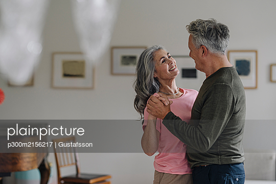 Happy senior couple dancing in living room at home - p300m2156217 by Gustafsson
