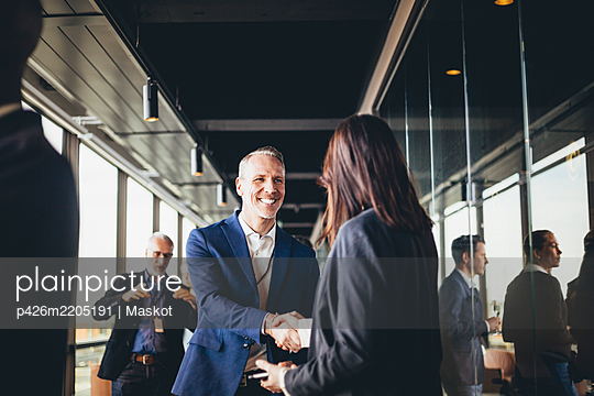 Smiling male entrepreneur shaking hands with businesswoman at workplace - p426m2205191 by Maskot
