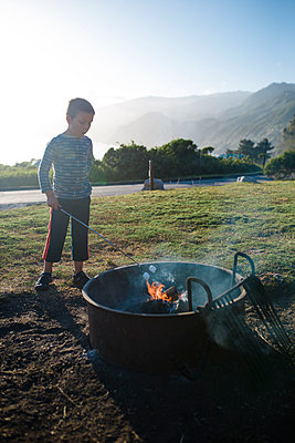 Full length of boy roasting marshmallows in campfire on field - p1166m2112350 by Cavan Images