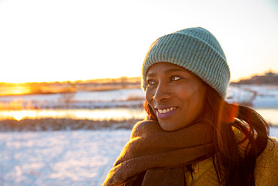 Smiling beautiful woman wearing scarf during winter while looking away - p300m2287730 by Frank van Delft