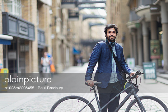 Portrait confident businessman with bicycle in city street - p1023m2208455 by Paul Bradbury