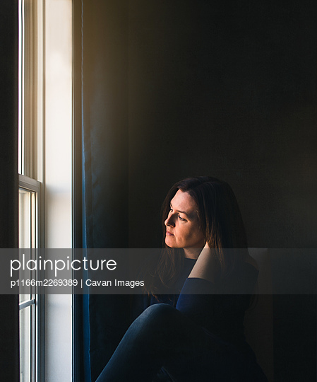 Woman sitting alone in a dark room looking out of the window. - p1166m2269389 by Cavan Images