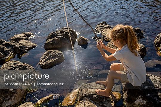 Mädchen angelt am Seeufer - p1355m1574071 von Tomasrodriguez