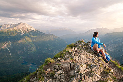 Austria, Tyrol, woman on a hiking trip in the mountains sitting on peak - p300m2083342 by Florian Küttler