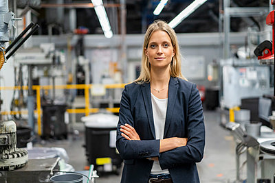 Confident businesswoman with arms crossed at factory - p300m2298917 by Daniel Ingold