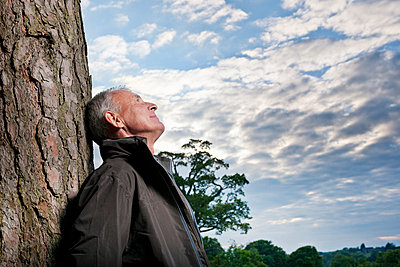 Man leaning against tree outdoors - p429m712140f by Colin Hawkins