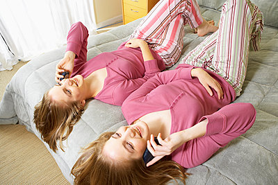 Caucasian twin teenage girls talking on cell phones - p555m1420374 by Tanya Constantine