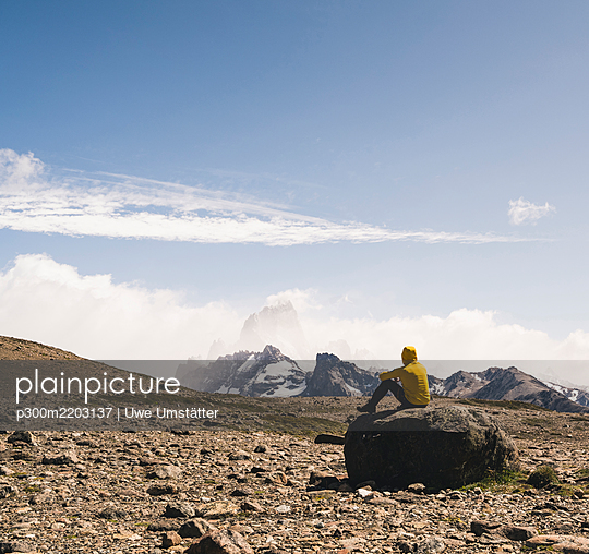 Male hiker looking at landscape against sky while sitting on rock, Patagonia, Argentina - p300m2203137 by Uwe Umstätter