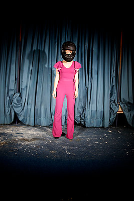 Woman with motorcycle helmet against stage curtain - p1105m2254497 by Virginie Plauchut