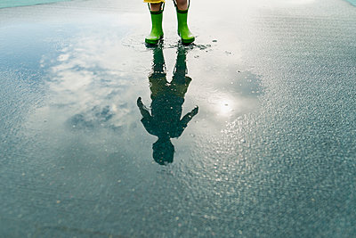 Reflection of boy in rubber boots standing in puddle - p1166m1186132 by Cavan Images