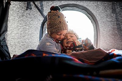 Smiling siblings sitting in roof tent - p1166m1543200 by Cavan Images