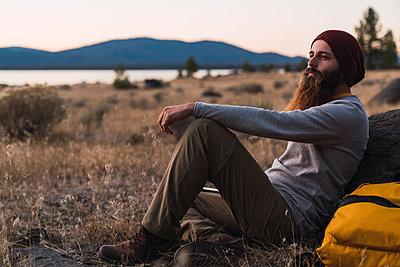 USA, North California, bearded young man having a break on a hiking trip near Lassen Volcanic National Park - p300m2059017 by Kike Arnaiz