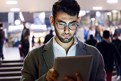 Germany, Munich, portrait of young businessman using digital tablet at central station - p300m2070087 von Tom Chance