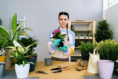 Young woman working in a gardening laboratory or plant shop - p300m2275410 von Giorgio Fochesato