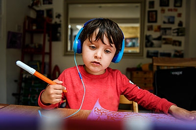 A five year old boy in blue headphones having an interactive learning session, home schooling.  - p429m2190386 by Bonfanti Diego