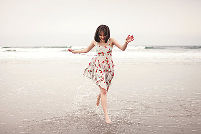 Caucasian woman running in waves on beach - p555m1408901 by Shestock