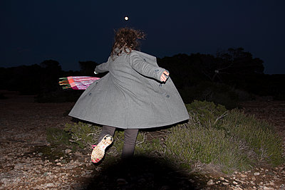 Woman in coat spinning under full moon - p583m1083770 by Kristina Williamson