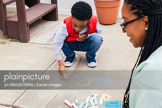 Boy using chalk to draw on concrete while mother smiles and helps - p1166m2279394 by Cavan Images